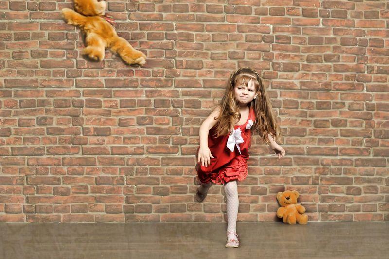 Child throwing teddy bear